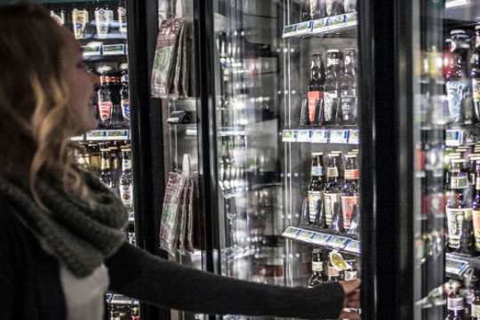 woman selecting craft beer from retailer
